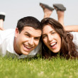 Couple laying down in the grass — Foto de Stock