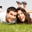 Couple laying down in the grass — Stockfoto