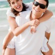 Young man piggyback his girlfriend - Stock Photo