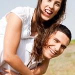 Smiling young couple piggybacking — Stock Photo