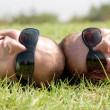 Happy young couple smiling on a lawn — Stock Photo