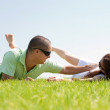 Young man play with his wife on a grass — Stock Photo
