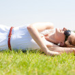 Happy young woman laying on grass field — Stock Photo