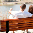 Young couple seated at the wooden bench — Foto de Stock