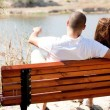 Young couple seated at the wooden bench — Foto de stock #1149078