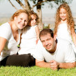 Family of four lying in grass - Stockfoto