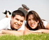 Casal jovem feliz deita na grama — Fotografia Stock