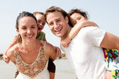 Couple With Children On Backs — Stock Photo