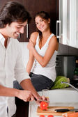 Boyfriend sliceing tomotos in kitchen — Stock Photo