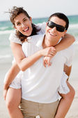 Young man piggyback his girlfriend — Stock Photo