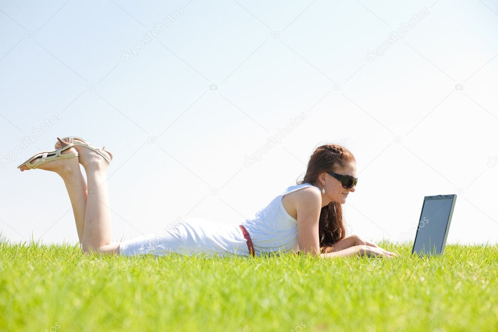 A cute young female lying on the grass in the park using a laptop — Stock Photo #1145937