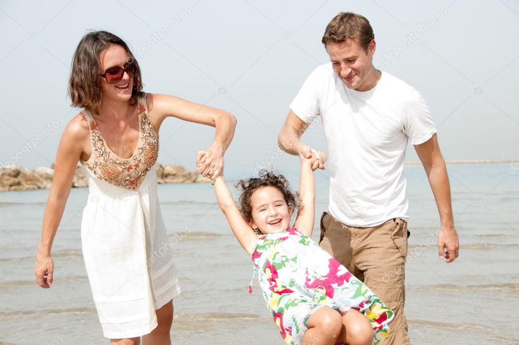 Young couple embracing and enjoying with young daughter on the beach — Stock Photo #1147348