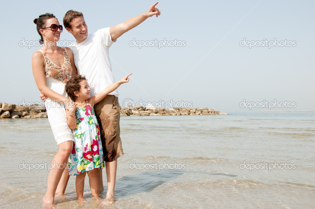 Happy family standing with young daughter in the beach and see Something — Stock Photo #1147426