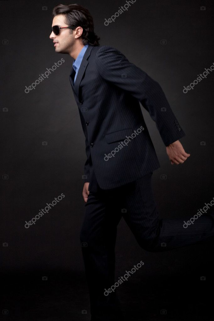 Young business man side view in isolated black background  Stock Photo #1148118