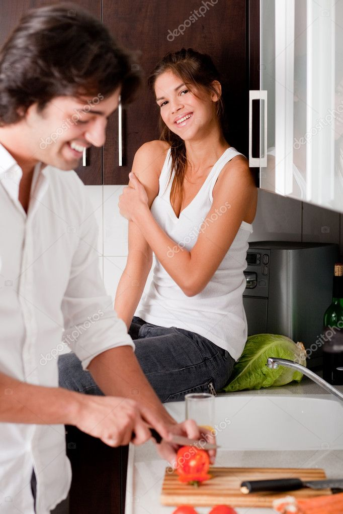Boyfriend sliceing tomottos with his girlfriend in kitchen — Stock Photo #1148187