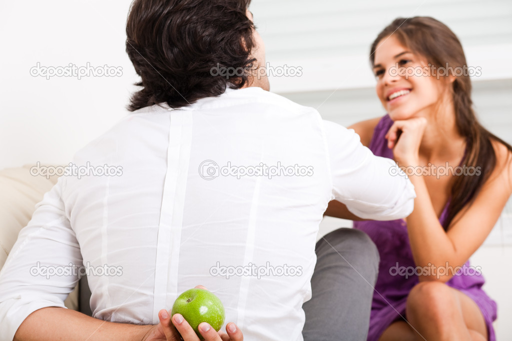 Young couple sitting on the sofa,man hiding fruit from his girlfriend — Stock Photo #1148393
