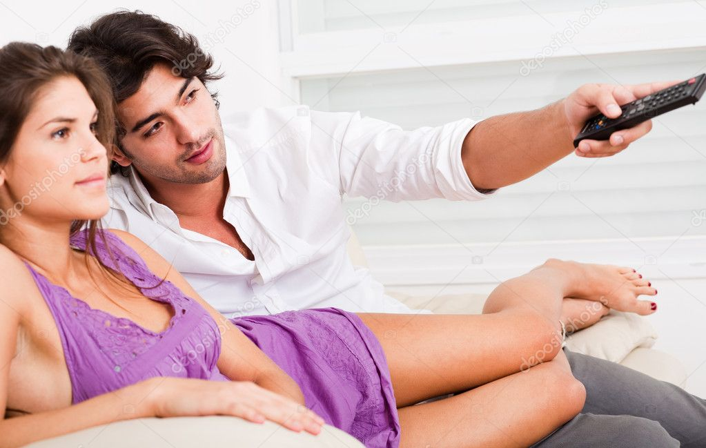 Happy young couple watch Tv by laying on the sofa — Stock Photo #1148405