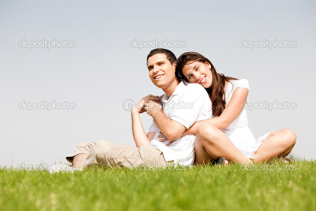 Happy young women with arms around her husband and laying on his shoulder in a park — Stock Photo #1148491