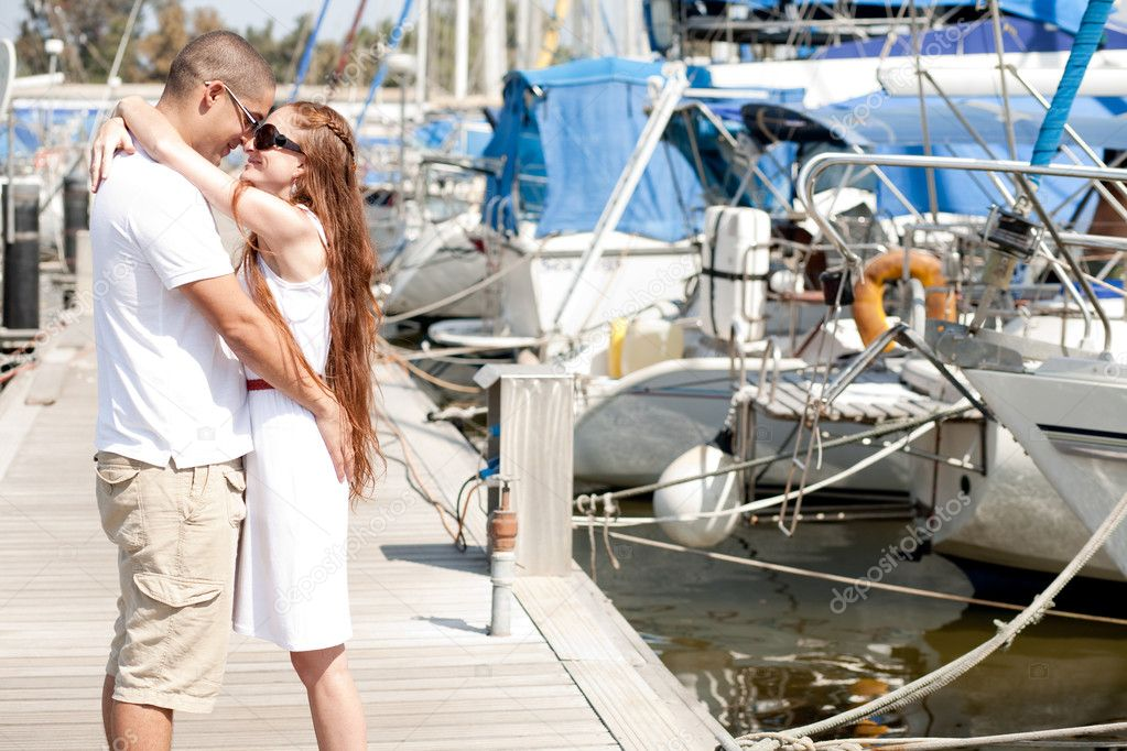 Young romantic couple hugging and standing at the harbor — Stock Photo #1149098