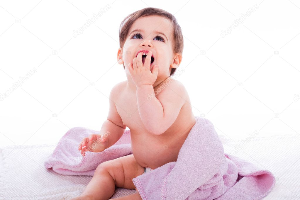 Baby laughing with open mouth sitting on a purple towel in a white isolated background — Stock Photo #1244124