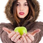 Yeşil elma gösterilen güzel genç bayan — Stok fotoğraf