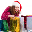 Santa girl looking into shopping bags — Stock Photo