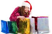 Santa girl looking into shopping bags — Stock Photo
