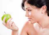 Beautiful woman holding a green apple — Stock Photo