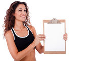 Fitness woman showing a blank clip board — Stock Photo