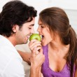 Young couple biting green apple — Stock Photo