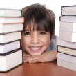 Young school boy surrounded by books — Stock Photo