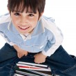 Top angle image of kid sitting on books — Stock Photo