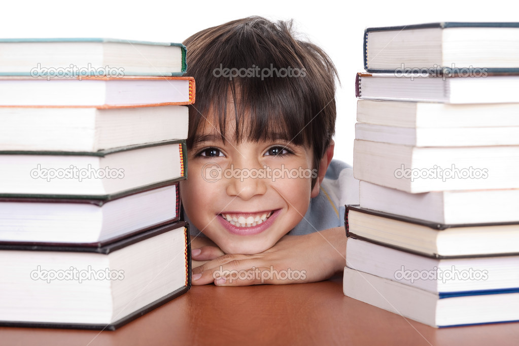 Happy young school boy surrounded by books on white background — Stock Photo #1960908