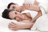 Loving husband and wife lying in bed — Stock Photo