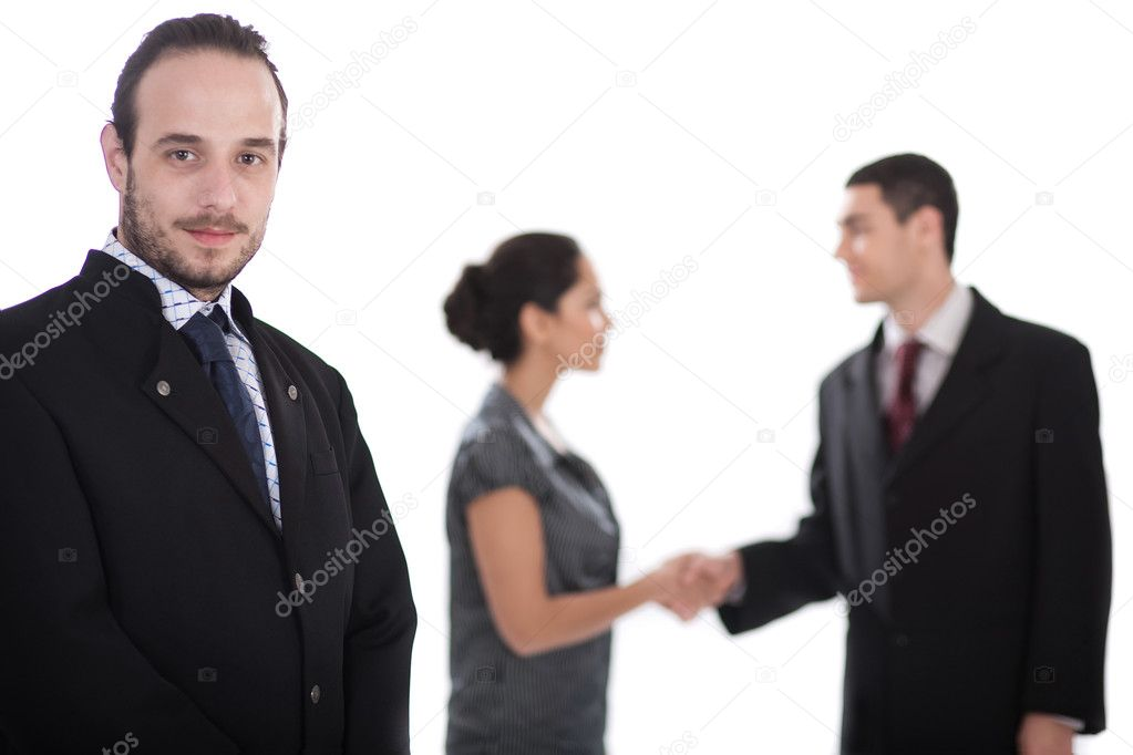 Handsome business man looking at us, two collegues giving shakehand out of focus in isolated white background — Stock Photo #2007097