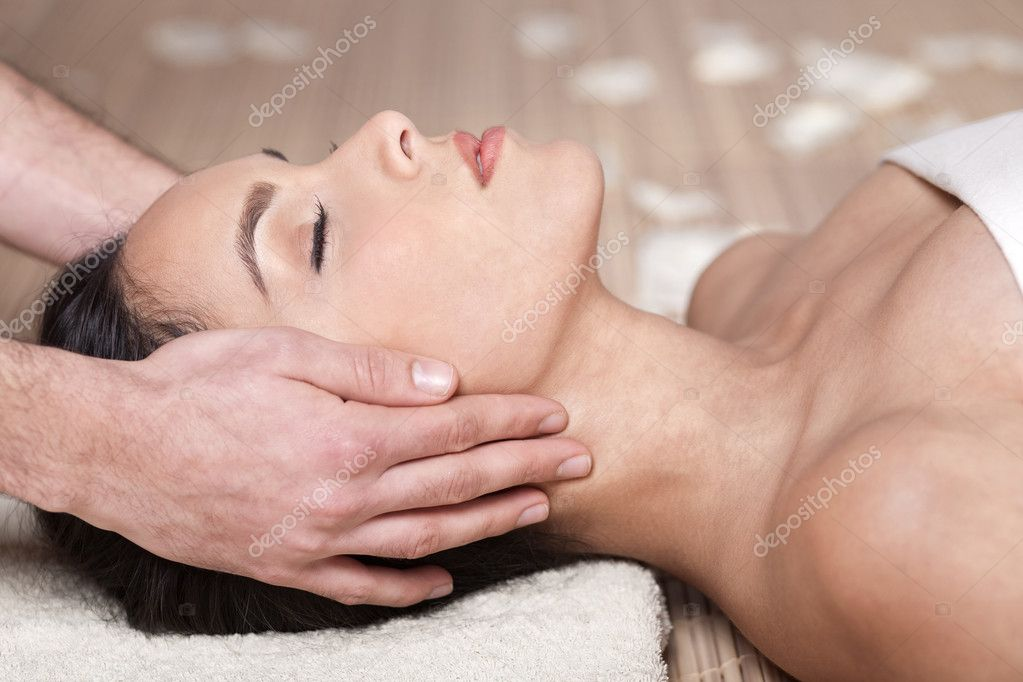 Happy woman receiving head massage over bamboo mat  Stock Photo #2120441