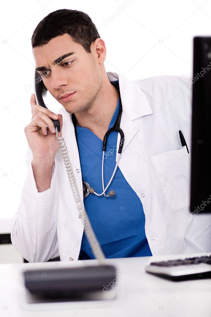 Caucasian male doctor sitting at the desk with computer talking over phone in white background — Stock Photo #2122061