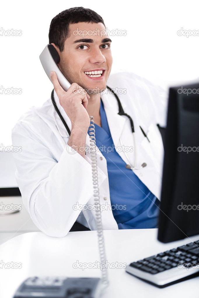 Smiling young physician sitting at his desk talking over phone in white background — Stock Photo #2122156
