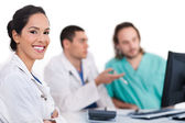 Smiling young doctor with other doctors — Stock Photo