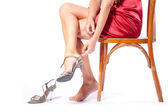 The woman puts shoes sitting on a chair — Stock Photo