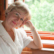 The mature woman at the open window — Stock Photo