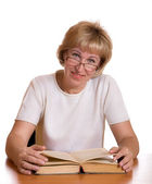 The mature woman with book behind a tab — Stock Photo