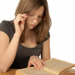 The girl in glasses reads the book — Stock Photo