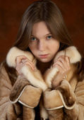 The girl in a fur coat on motley backgro — Stock Photo
