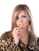 The girl in fur coat eats tangerine — Stock Photo