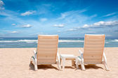 Two chaise longues on beach near ocean — Stock Photo