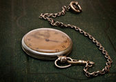 Old clock with chain lying on rough gree — Stockfoto