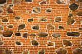 Brick wall with embedded stones — Stock Photo