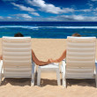 Couple in beach chairs holding hands nea — Foto de Stock