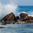 Foto Stock: Waves breaking against rocks